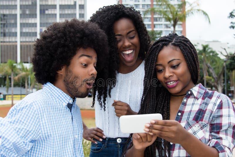 Groep Afrikaanse Amerikaanse mensen die telefoon bekijken royalty-vrije stock afbeelding