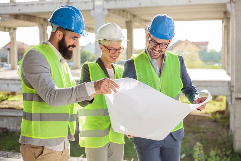 Groep architecten of partners die plattegronden op een bouwwerf bespreken stock afbeeldingen