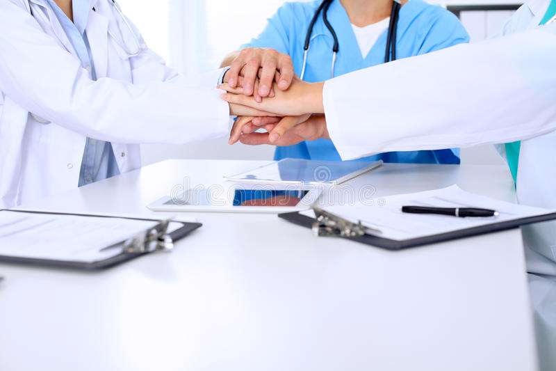 Groep artsen die bij handen na vergadering aansluiten zich Het succesvolle medische team is klaar voor het helpen stock foto's