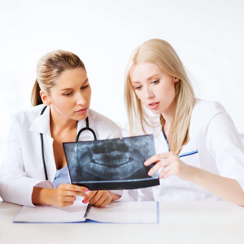 Groep artsen die röntgenstraal bekijken stock afbeeldingen
