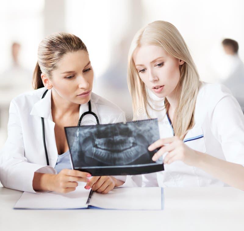 Groep artsen die röntgenstraal bekijken stock foto
