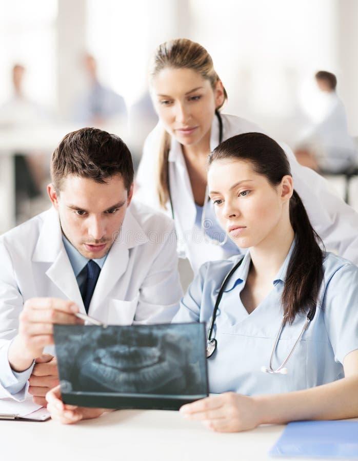 Groep artsen die röntgenstraal bekijken stock fotografie