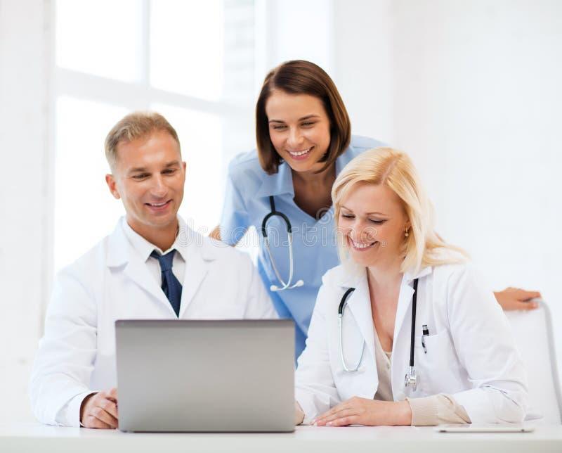 Groep artsen die tabletpc bekijken stock foto