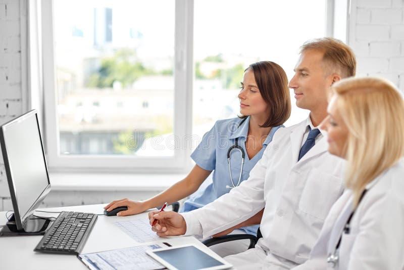 Groep artsen met computer bij het ziekenhuis stock afbeeldingen