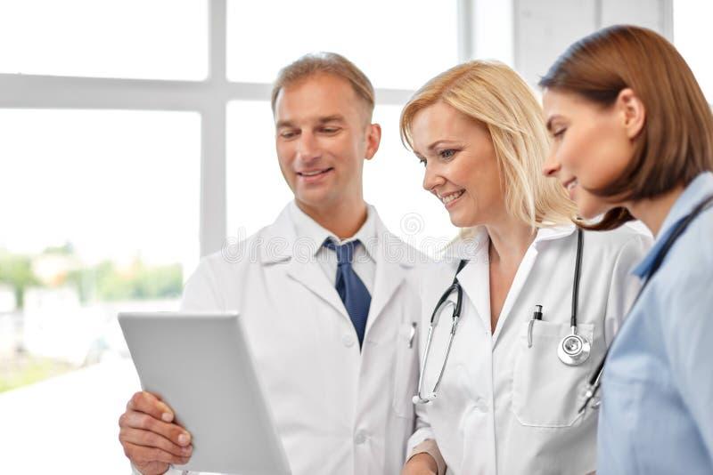 Groep artsen met tabletcomputer bij het ziekenhuis stock foto's