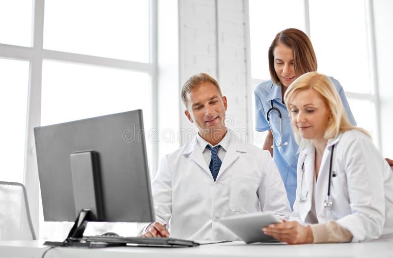 Groep artsen met tabletcomputer bij het ziekenhuis stock afbeelding