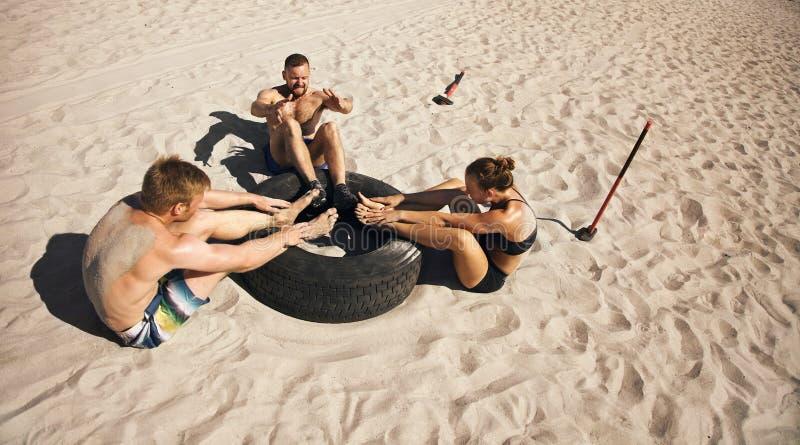 Groep atleten die crossfit oefeningsroutine op strand doen stock fotografie