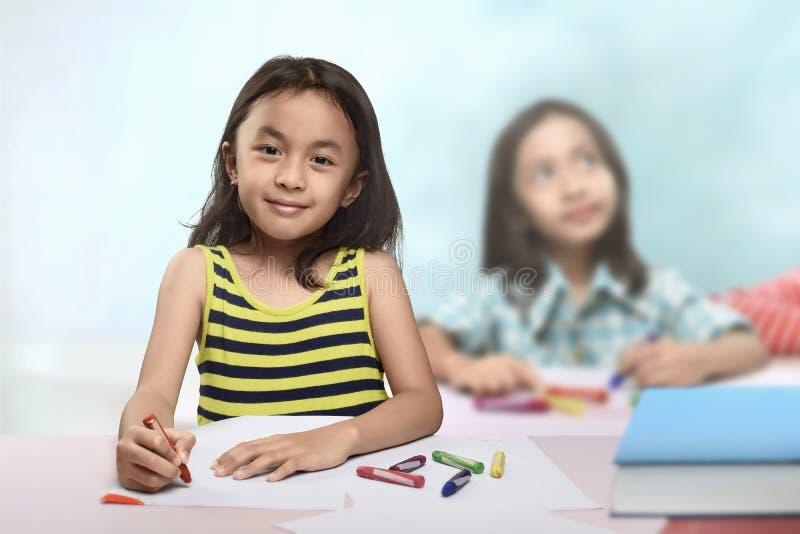 Groep Aziatisch meisje bij de lijst en tekening met kleurpotlood stock afbeeldingen