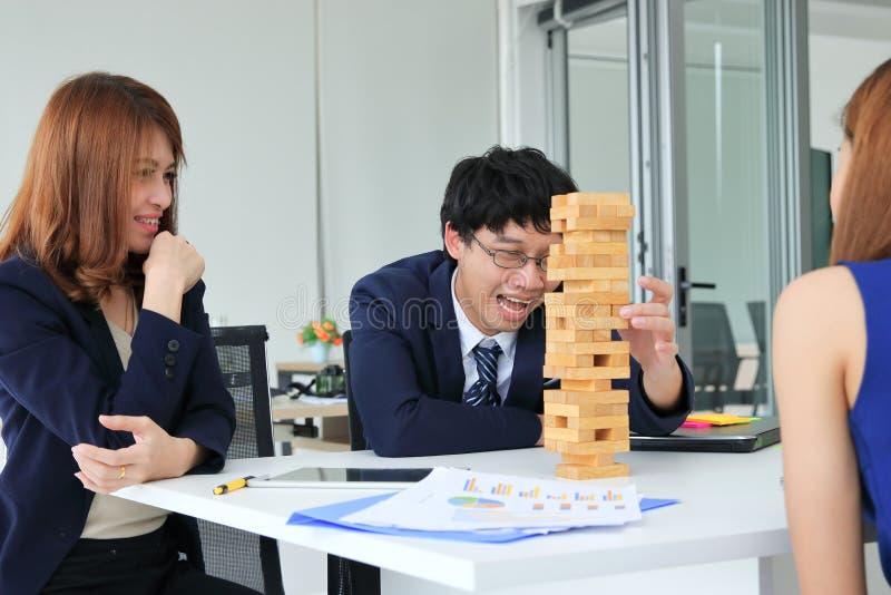 Groep Aziatische bedrijfsmensen die pret samen in werkplaats van bureau hebben stock foto's
