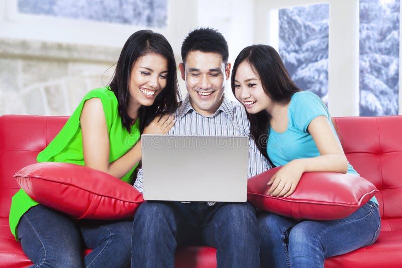 Groep Aziatische mensen die laptop op bank met behulp van royalty-vrije stock fotografie