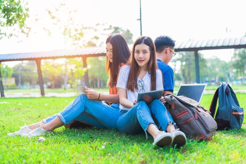 Groep Aziatische student tablet in openlucht gebruiken en laptop die op grasgebied bij Technologie en Onderwijs het leren concept royalty-vrije stock foto's