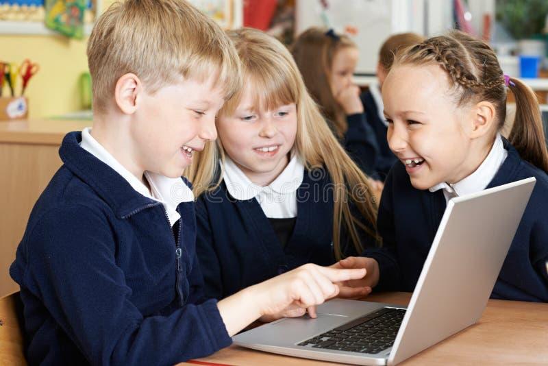 Groep Basisschoolkinderen die in Computer samenwerken stock foto