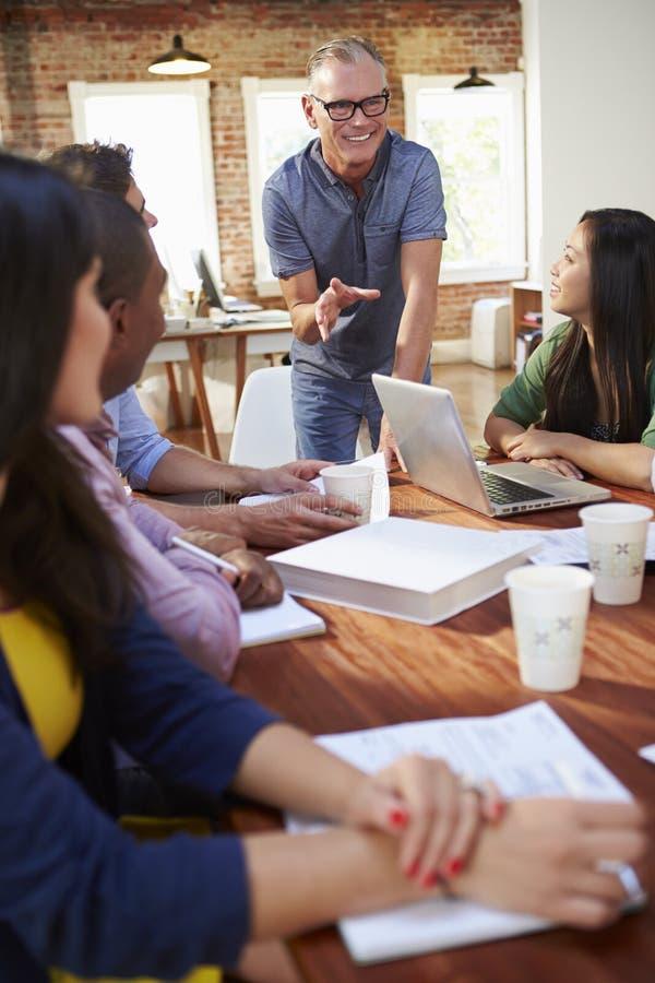 Groep Beambten die Ideeën samenkomen te bespreken stock foto's