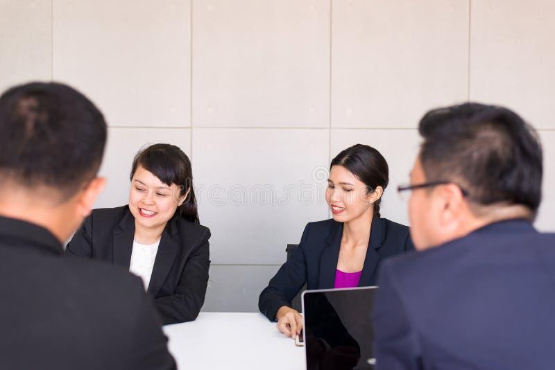 Groep bedrijfs Aziatische mensen die en het communiceren ontmoeten werken terwijl samen het zitten bij ruimtebureau, Groepswerkco royalty-vrije stock foto