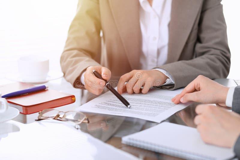 Groep bedrijfsmensen of advocaten die contractdocumenten bespreken die bij de lijst, close-up zitten stock afbeeldingen