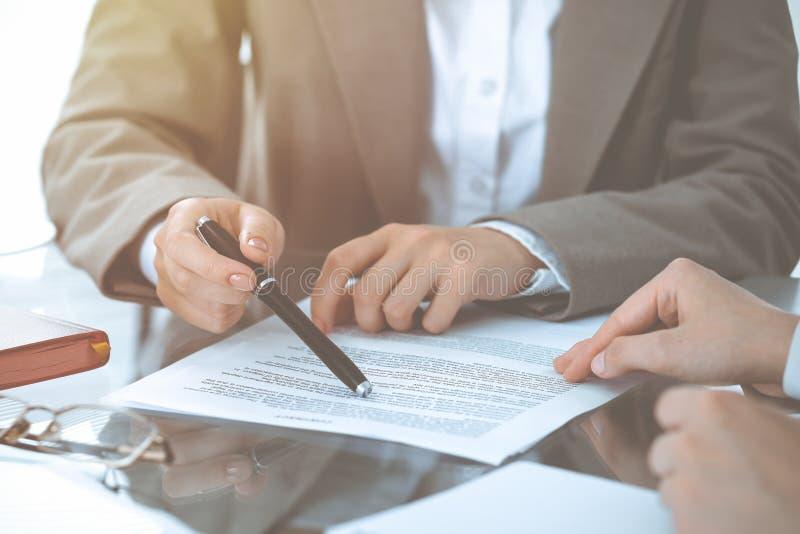 Groep bedrijfsmensen of advocaten die contractdocumenten bespreken die bij de lijst, close-up zitten stock afbeelding