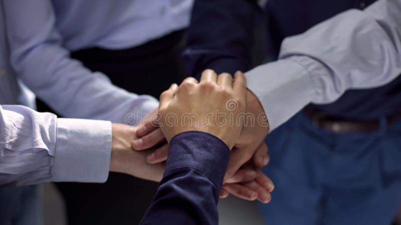 Groep bedrijfsmensen die handen, team de bouw opleiding, samenwerking stapelen stock afbeelding