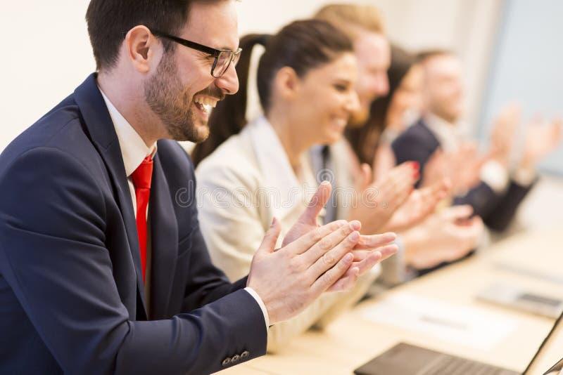 Groep bedrijfsmensen die hun handen slaan op de vergadering royalty-vrije stock afbeeldingen