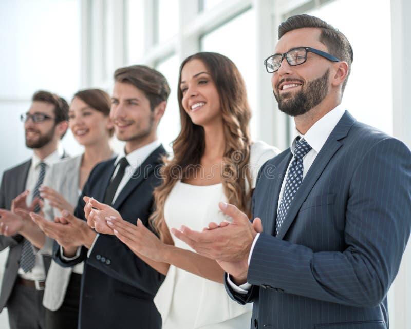 Groep bedrijfsmensen die iemand toejuichen die zich in offi bevinden stock afbeelding