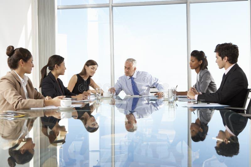 Groep Bedrijfsmensen die Raadsvergadering hebben rond Glaslijst stock afbeelding