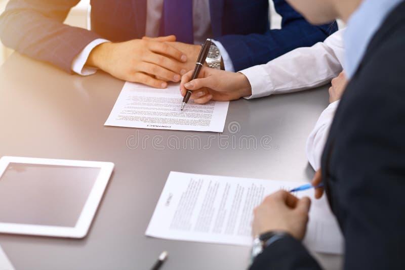 Groep bedrijfsmensen en advocaat die contractdocumenten bespreken die bij de lijst, close-up zitten De zakenman ondertekent stock afbeelding