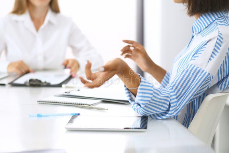 Groep bedrijfsmensen op vergadering in bureau, close-up Team van twee vrouwen die overeenkomst bespreken Onderhandelingsconcept royalty-vrije stock afbeeldingen