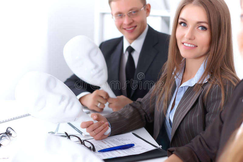 Groep bedrijfsmensen op vergadering De bedrijfsmensen verbergen hun emoties onder het masker van vertrouwen tijdens Th stock foto