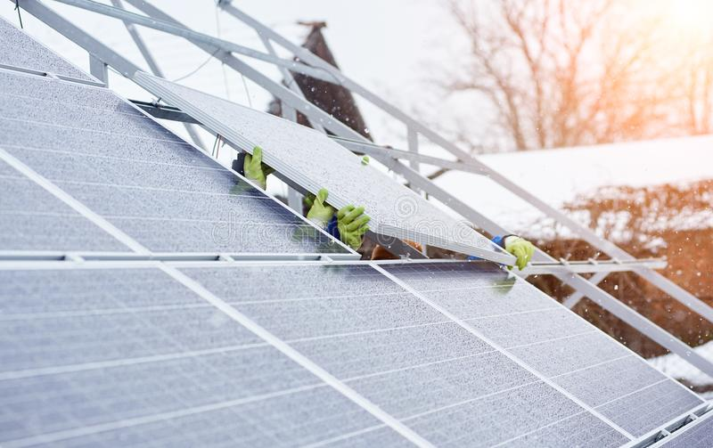 Groep beroeps die photovoltaic zonnepanelen installeren op het dak van modern huis tijdens sneeuw de wintertijd royalty-vrije stock fotografie