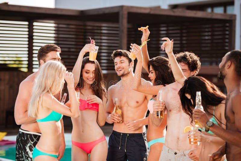 Groep beste vrienden die partij hebben door zwembad royalty-vrije stock afbeelding