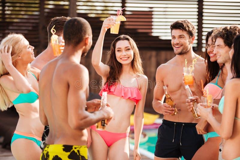 Groep beste vrienden die partij hebben door zwembad royalty-vrije stock foto's