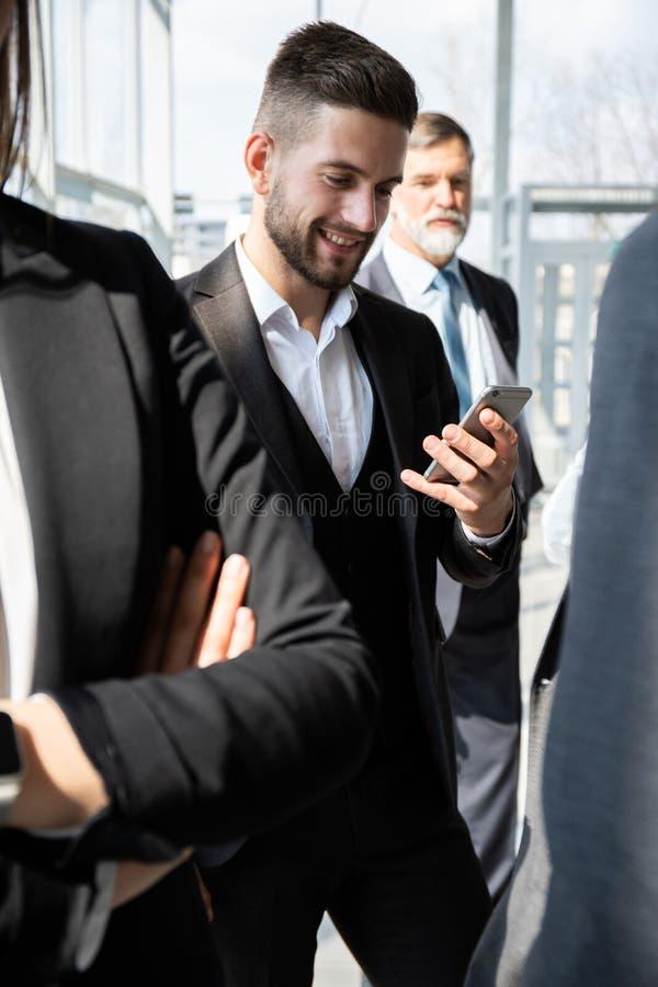 Groep Bezig Bedrijfsmensenconcept Commercieel team die het werk in de bureaubouw gang bespreken stock afbeelding
