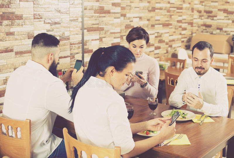 Groep bezige vrienden die smartphones bij restaurant gebruiken stock afbeelding