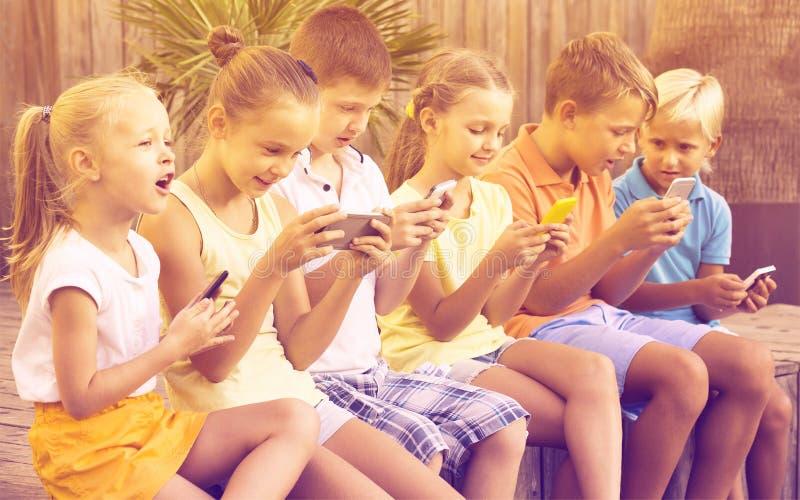 Groep blije kinderen die met mobiele telefoons in openlucht spelen stock afbeeldingen