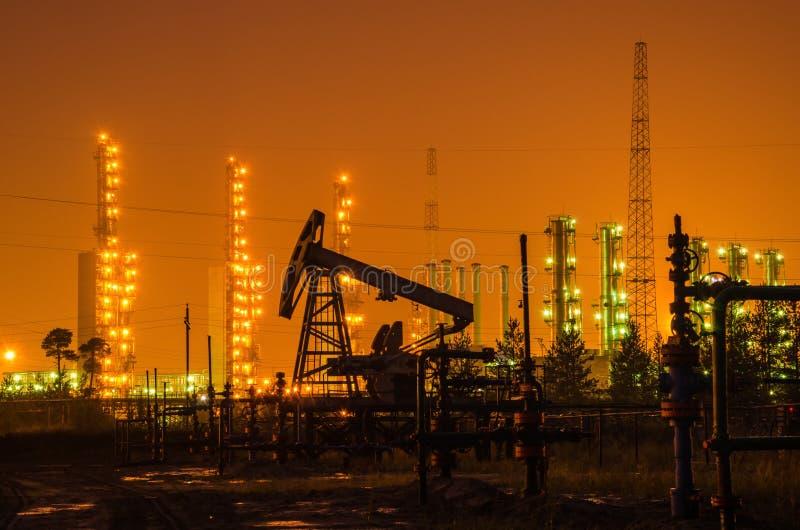Groep boorplatforms en bron bij de achtergrond van raffinaderij stock foto's