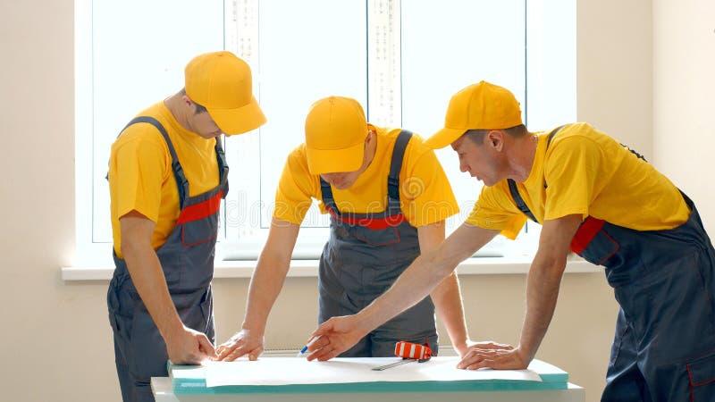 Groep bouwers die het bouwproject bekijken stock foto