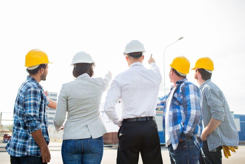 Groep bouwers en architecten bij bouwterrein stock afbeelding