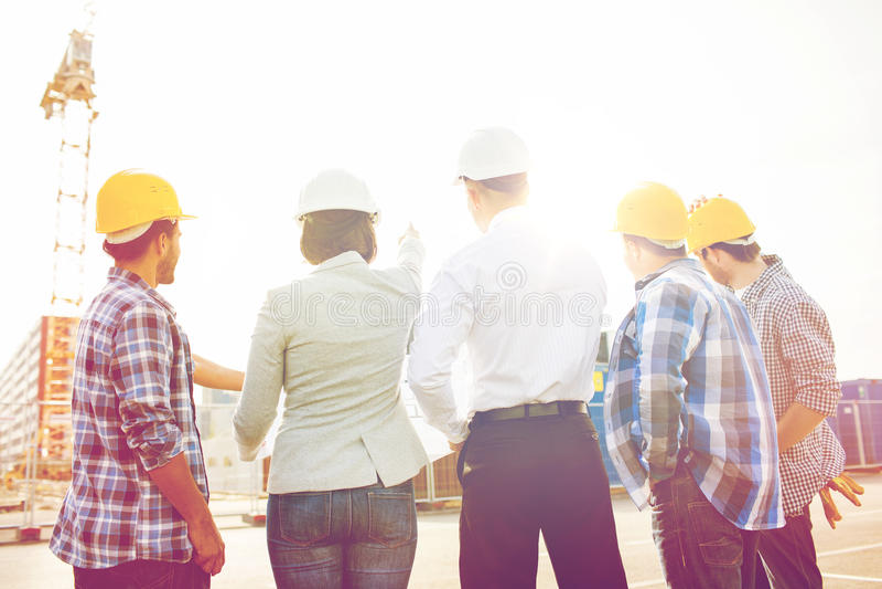 Groep bouwers en architecten bij bouwterrein stock afbeeldingen