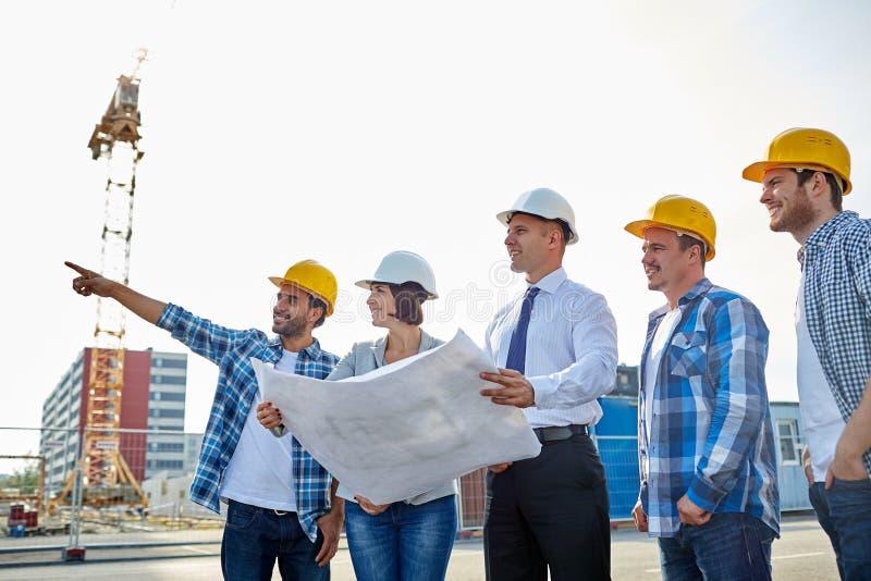Groep bouwers en architecten met blauwdruk stock foto's