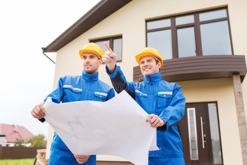 Groep bouwers met blauwdruk die vinger richt royalty-vrije stock afbeelding