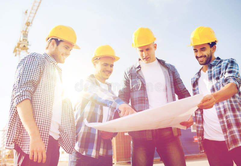 Groep bouwers met tabletpc en blauwdruk stock fotografie