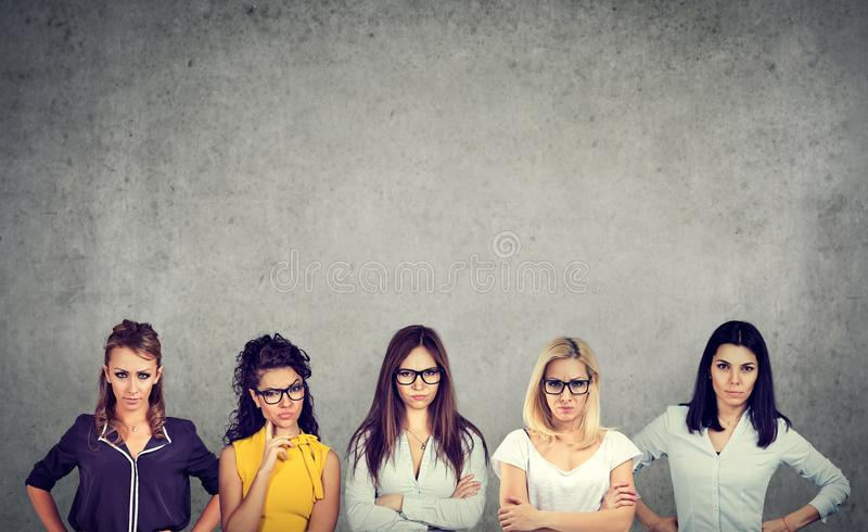 Groep boze negatieve jonge vrouwen die camera bekijken terwijl status tegen concrete muurachtergrond stock foto's