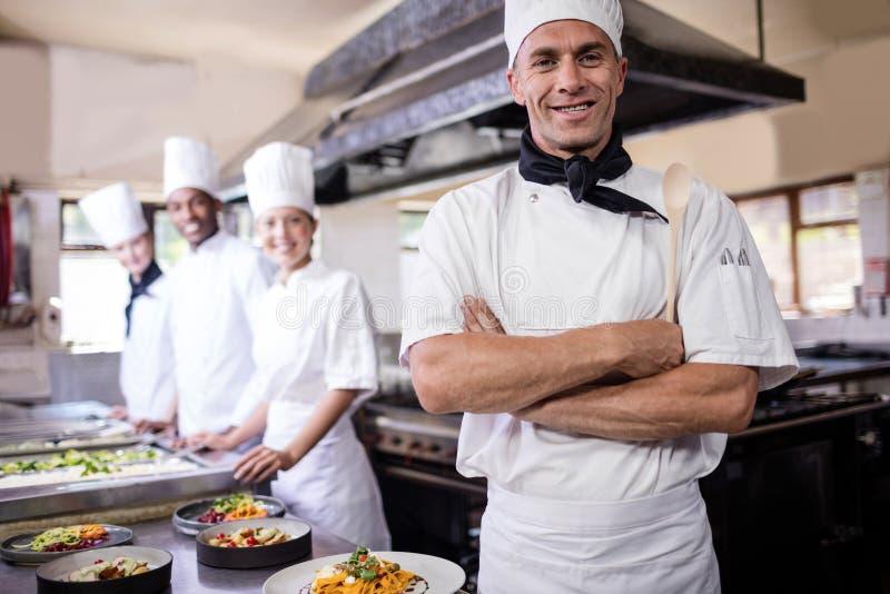 Groep chef-koks die zich met die wapens bevinden in keuken worden gekruist stock foto