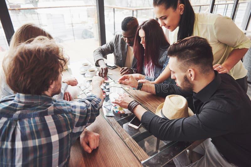 Groep creatieve multietnic vrienden die bij houten lijst zitten Mensen die pret hebben terwijl het spelen van raadsspel royalty-vrije stock foto
