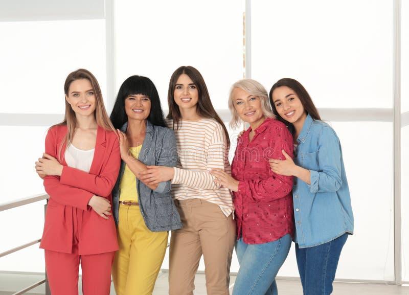 Groep dames dichtbij venster het concept van de vrouwenmacht stock afbeelding