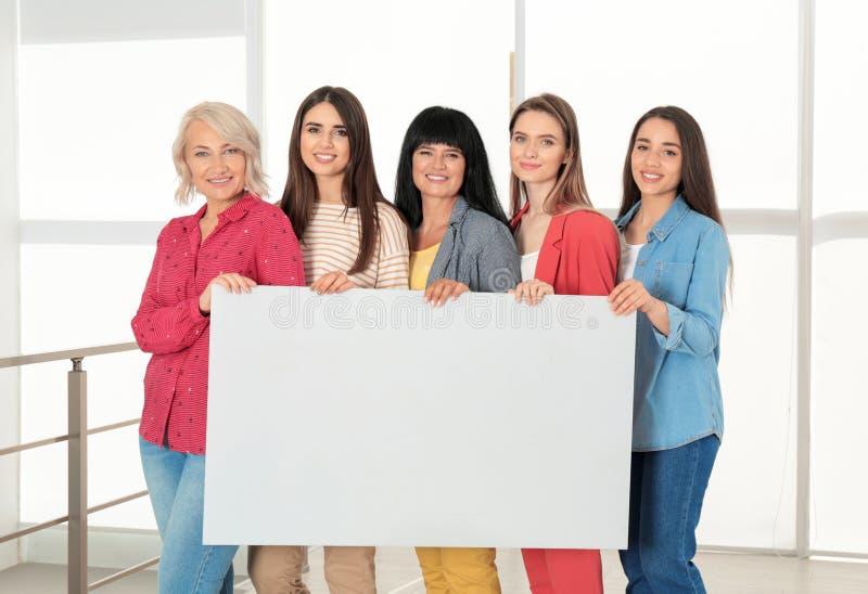 Groep dames met lege affiche dichtbij venster binnen het concept van de vrouwenmacht royalty-vrije stock afbeeldingen