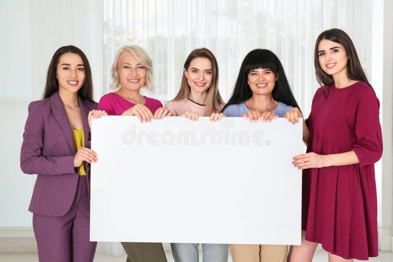 Groep dames met lege affiche dichtbij venster binnen het concept van de vrouwenmacht royalty-vrije stock foto