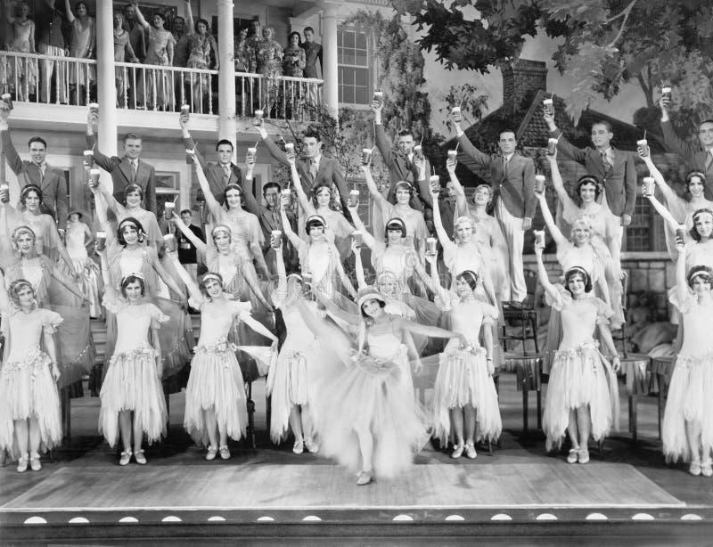 Groep dansers die zich op een stadium met hun wapens in de lucht en een drank in hun handen bevinden (Alle afgeschilderde persone stock foto's