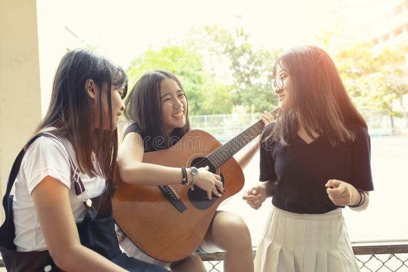 Groep de Aziatische emotie die van het tienergeluk Spaanse gitaar op plaats spelen royalty-vrije stock afbeeldingen