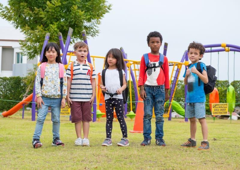 Groep de kinderen die van de diversiteitsschool bij speelplaats in soort spelen stock foto