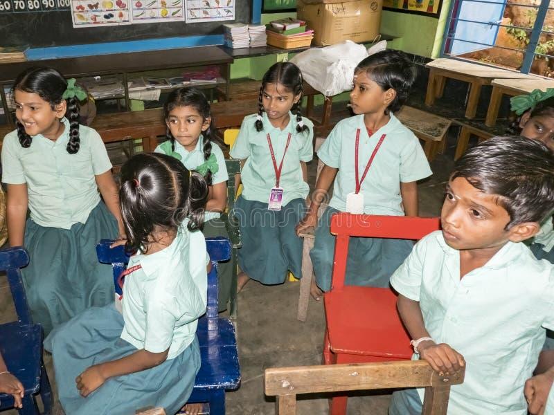 Groep de klasgenoten die van kinderenvrienden zitting op stoelen bestuderen binnen op de school Schooljonge geitjes die van vrien stock fotografie